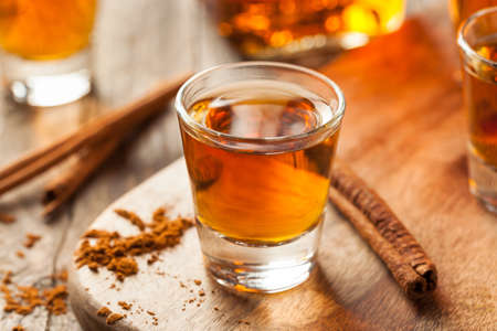 shot: Cinnamon Whiskey Bourbon in a Shot Glass Ready to Drink Stock Photo