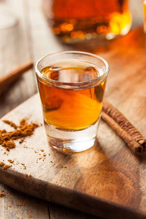 bourbon: Cinnamon Whiskey Bourbon in a Shot Glass Ready to Drink Stock Photo