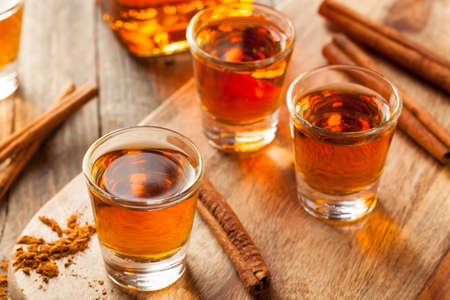 spirits: Cinnamon Whiskey Bourbon in a Shot Glass Ready to Drink Stock Photo