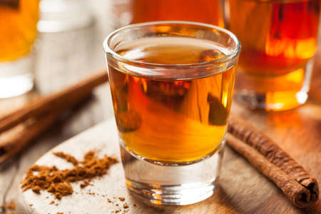 liquor glass: Cinnamon Whiskey Bourbon in a Shot Glass Ready to Drink Stock Photo