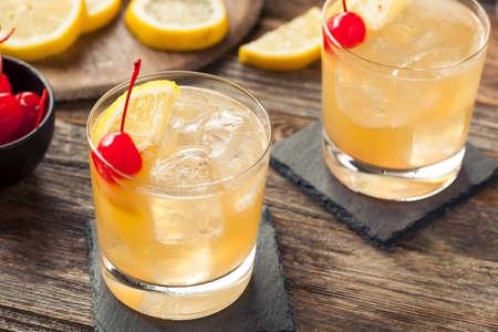 Selbst gemachte Whiskey Sour Cocktail Drink mit einer Kirsche Zitrone Standard-Bild