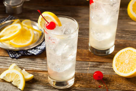 garnish: Refreshing Classic Tom Collins Cocktail with a Cherry and Lemon Slice Stock Photo