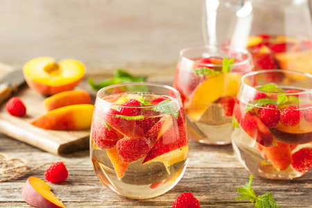 Homemade Sparkling White Wine Sangria with Peaches and Raspberries Stock Photo