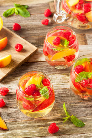 fruta tropical: Homemade Sparkling White Wine Sangria with Peaches and Raspberries Foto de archivo