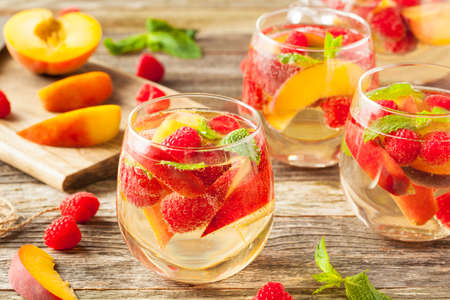 white wine: Homemade Sparkling White Wine Sangria with Peaches and Raspberries Stock Photo