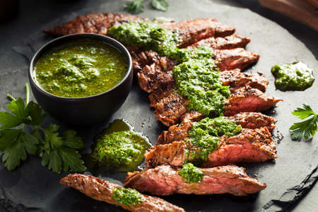 Homemade Cooked Skirt Steak with Chimichurri Sauce and Spices Stock Photo