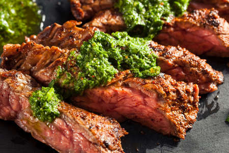 Homemade Cooked Skirt Steak with Chimichurri Sauce and Spices Archivio Fotografico
