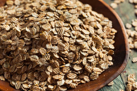 rye: Organic Rolled Rye Flakes in a Bowl Stock Photo