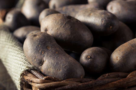 peel: Raw Organic Purple Potatoes in a Basket Stock Photo