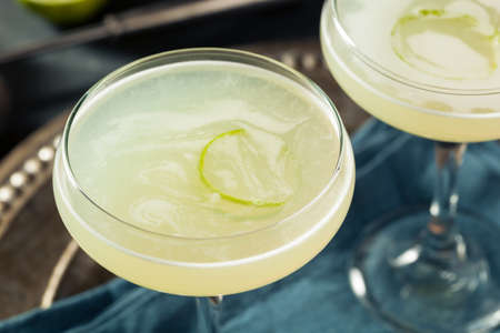 lemon wedge: Alcoholic Lime and Gin Gimlet with a Garnish Stock Photo