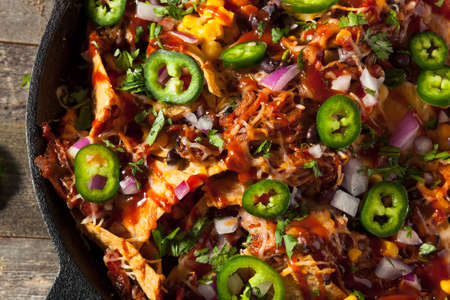 plates of food: Homemade Barbecue Pulled Pork Nachos with Cheese and Peppers