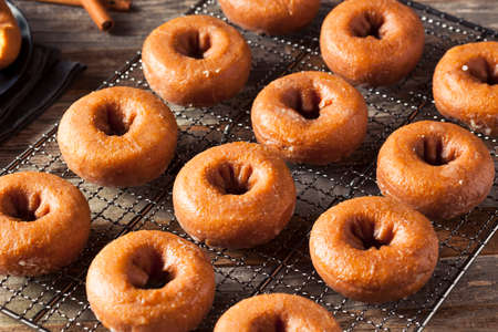 baking bread: Homemade Glazed Autumn Pumpkin Donuts Ready to Eat Stock Photo