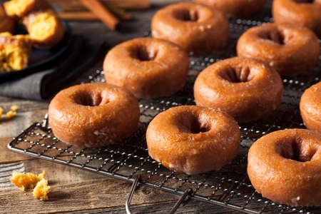 donut shape: Homemade Glazed Autumn Pumpkin Donuts Ready to Eat Stock Photo