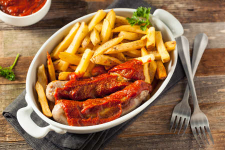 Homemade Currywurst and French Fries in a Bowl Stock Photo