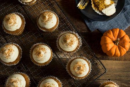 magdalenas: Dulce hecho en casa de la especia de calabaza con crema de vainilla de las magdalenas