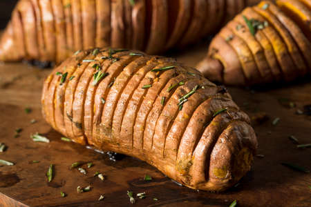 nutrition health: Homemade Organic Hasselback Sweet Potato with Fresh Herbs Stock Photo