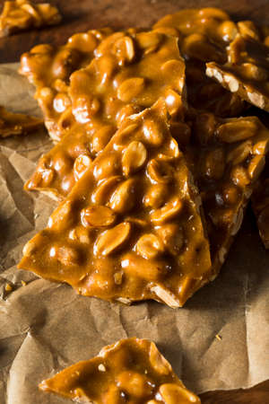 brittle: Homemade Holiday Peanut Brittle Broken into Pieces Stock Photo
