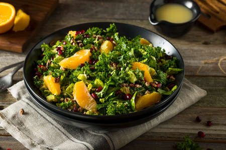 Raw Healthy Kale Winter Salad with Oranges and Pomegranate Seeds Stock Photo