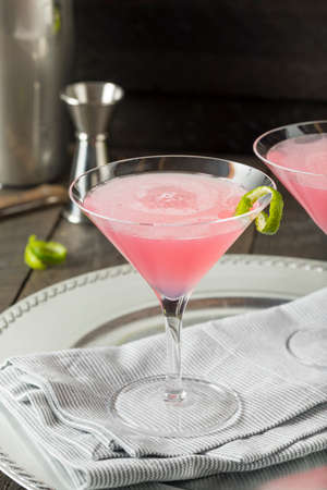 Homemade Pink Vodka Cosmopolitan Drink with a Lime Garnish Stock Photo