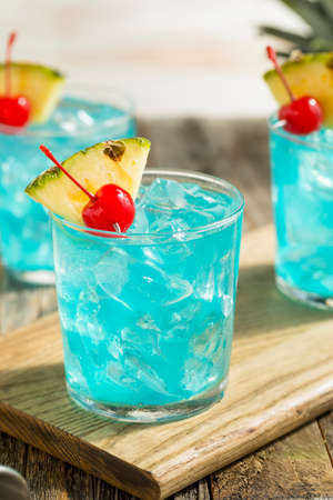 Refreshing Blue Hawaii Cocktail Punch with Pineapple and Cherry Stock Photo