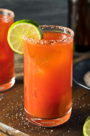 Homemade Michelada with Beer Salted Rim and Tomato Juice Imagens