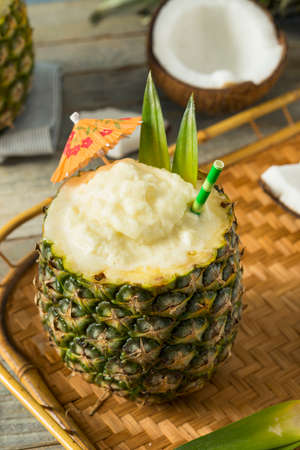 Frozen Pina Colada Cocktail in a Pineapple with a Garnish Stock Photo