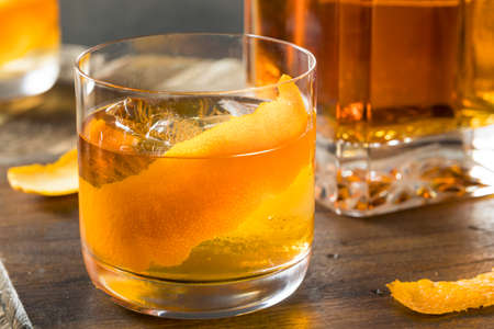 Cold Alcoholic Old Fashioned Bourbon Whiskey Cocktail with Orange Garnish Stock Photo