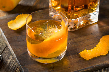 Cold Alcoholic Old Fashioned Bourbon Whiskey Cocktail with Orange Garnish Stock Photo