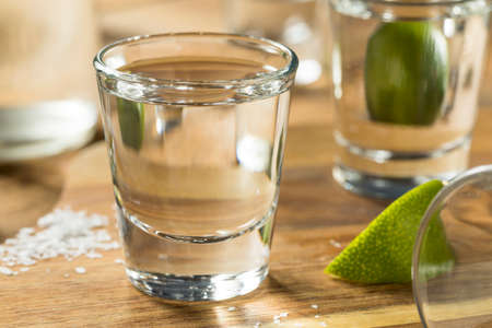 silver background: Alcohol Mezcal Tequila Shots with Lime and Salt