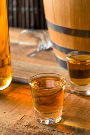 Alcoholic Brown Rum in a Shot Glass Ready to Drink Stock Photo