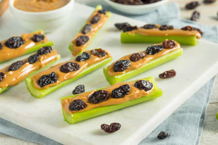 Homemade Ants on a Log Snack with Celery Peanut Butter and Raisins Imagens