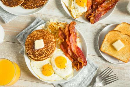 Desayuno americano completo saludable con huevos tocino y panqueques Foto de archivo - 84828903