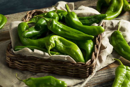 Raw Green Spicy Hatch Peppers in a Basket Archivio Fotografico