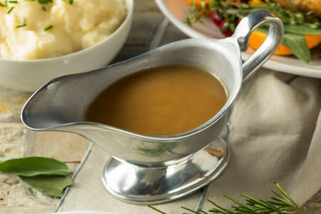 Hot Brown Organic Turkey Gravy in a Boat Standard-Bild