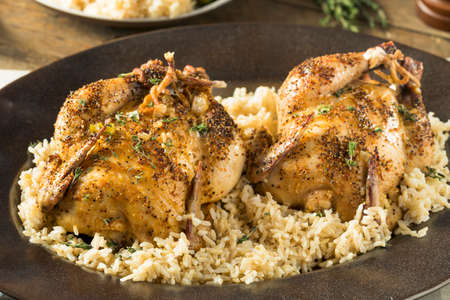 Herby Baked Cornish Game Hens with Rice and Veggies Stock Photo