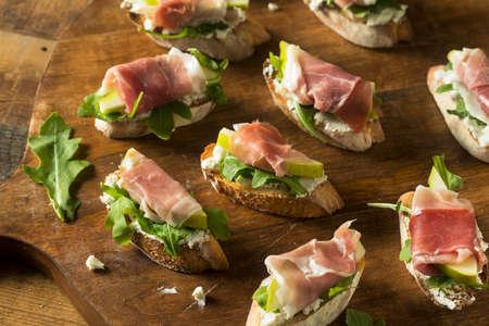 Homemade Prosciutto Pear Cheese Crostini with Arugula Imagens - 91479576