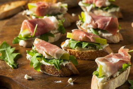 Homemade Prosciutto Pear Cheese Crostini with Arugula Banque d'images