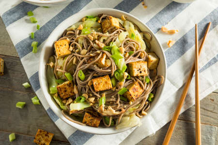 Homemade Asian Tofu Soba Noodle Bowl with Onions and Peanuts Stock Photo