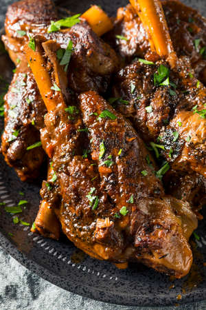 Homemade Braised Lamb Shanks with Sauce and Herbs Stock Photo
