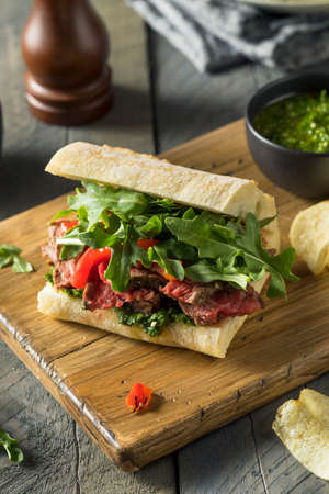 Homemade Beef Steak Sandwich with Chimichurri and Arugula Imagens
