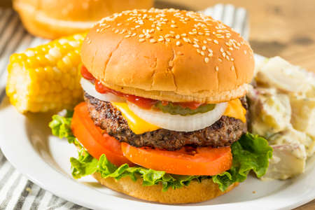 Memorial Day Backyard Babecue Meal with Hamburgers Hot dogs Salads and Chips Stock Photo
