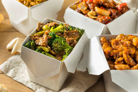 Spicy Chinese Take Out Food with Chopsticks and Fortune Cookies Stock Photo