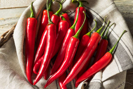 Raw Red Organic Hot Finger Peppers in a Basket Stock Photo