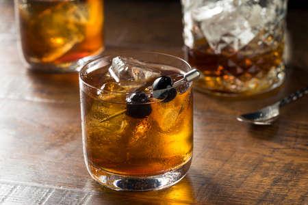 Boozy Manhattan Cocktail on the Rocks with a Cherry Garnish Stock Photo