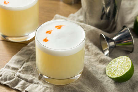 Homemade Pisco Sour Cocktail with Lime and Bitters