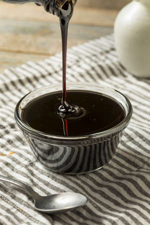 Organic Black Cane Sugar Molasses in a Bowl Reklamní fotografie - 106239893