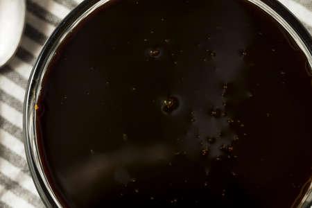 Organic Black Cane Sugar Molasses in a Bowl 写真素材
