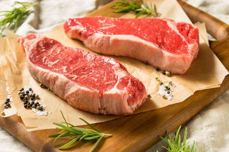 Raw Grass Fed NY Strip Steaks with Salt and Pepper Stok Fotoğraf - 108938213