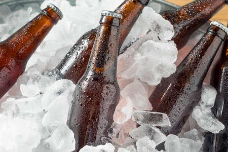Koude ijzige bierflessen in een koeler met ijs