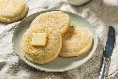 Hausgemachte gegrillte britische Crumpets mit Butter zum Frühstück Standard-Bild